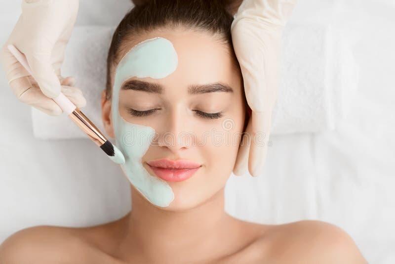 Kosmetolog som applicerar leraframsidamaskeringen p? kvinnaframsida fotografering för bildbyråer