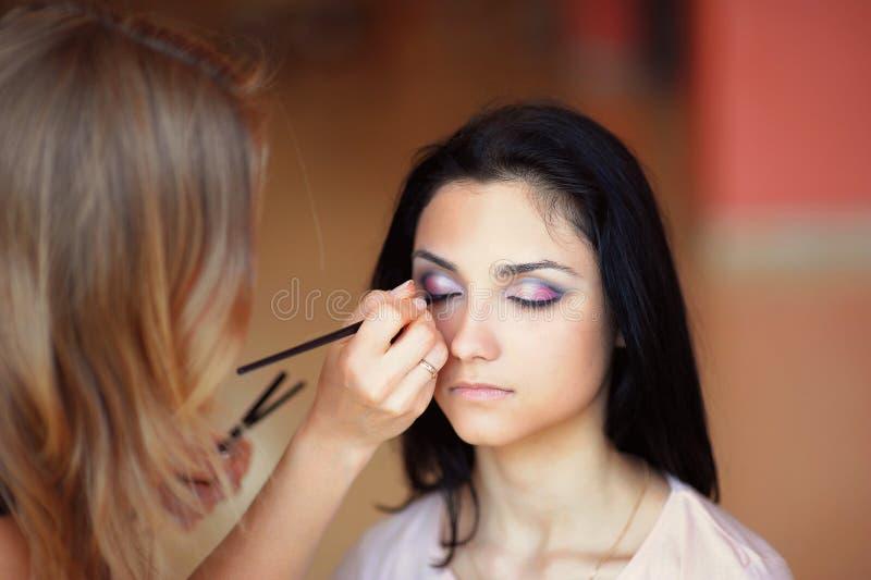Kosmetolog som applicerar makeupmodellkvinnan fotografering för bildbyråer