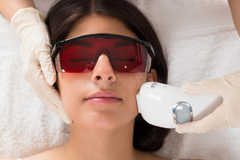 Kosmetolog som ger epilationlaser-behandling royaltyfri foto