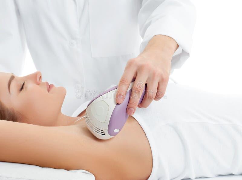 Kosmetolog som ger på epilationlaser-behandling till kvinnan underarm royaltyfria bilder