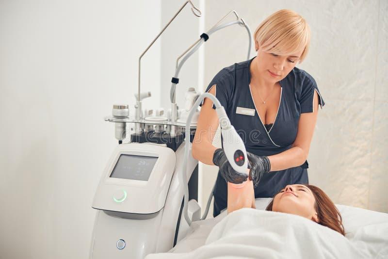 Kosmetolog som reducerar cellulit i armen på den kvinnliga patienten royaltyfria foton