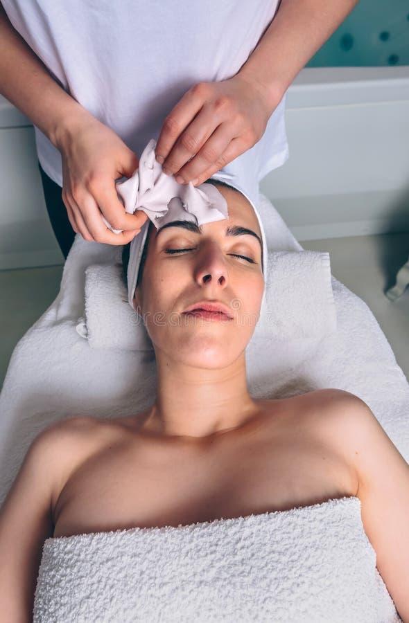 Kosmetolog som tar bort den ansikts- maskeringen till kvinnan i brunnsort royaltyfri fotografi