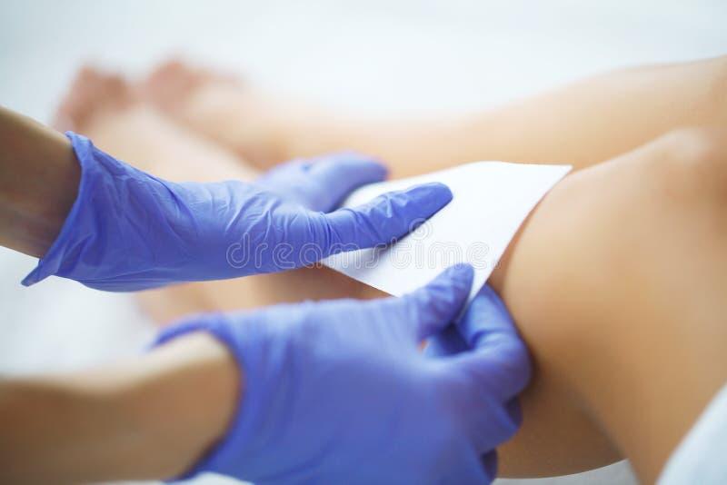 Kosmetolog som vaxar ett ben för kvinna` s royaltyfria foton
