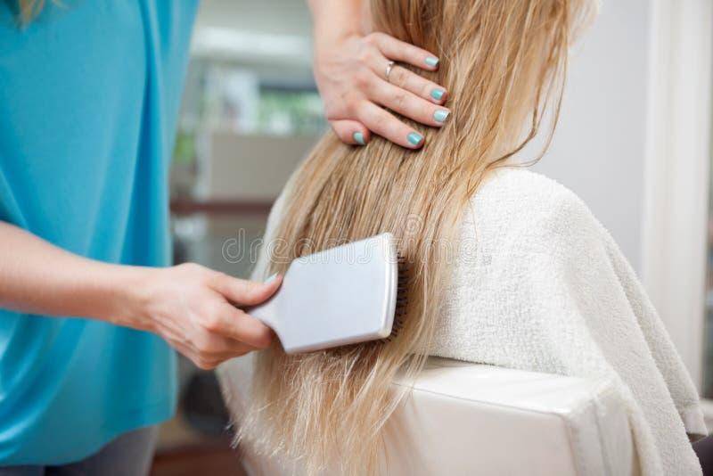 KosmetologCombing Hair Of kund fotografering för bildbyråer