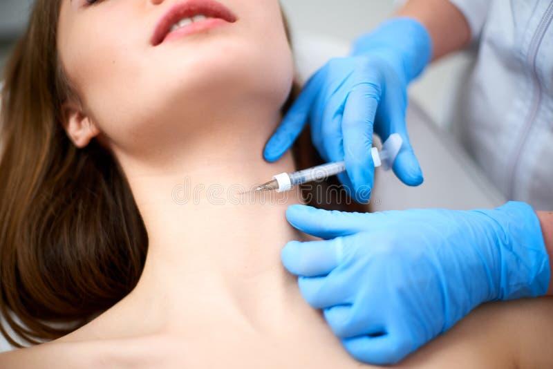 Kosmetologdoktor med den botulinum toxininjektionssprutan som gör injektionen till platysmal musikband Mesotherapy halsföryngring arkivfoton