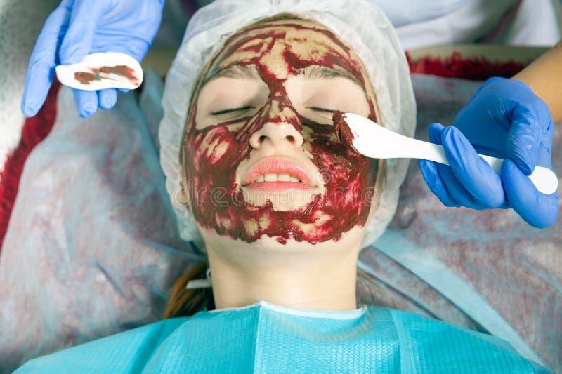 Kosmetologen gör en terapeutisk brunnsortmaskering fotografering för bildbyråer