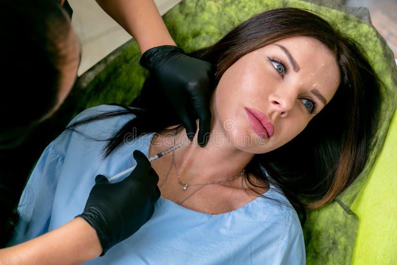Kosmetologen injicerar botulinum toxininjektioner i kvinnans hals Mellersta ålderkvinna på cosmetological tillvägagångssätt Sk?nh arkivbild