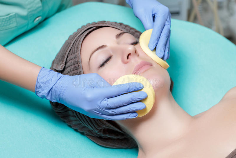 Kosmetologen rentvår hudkvinnan med svampen Perfekt lokalvård - c arkivfoto