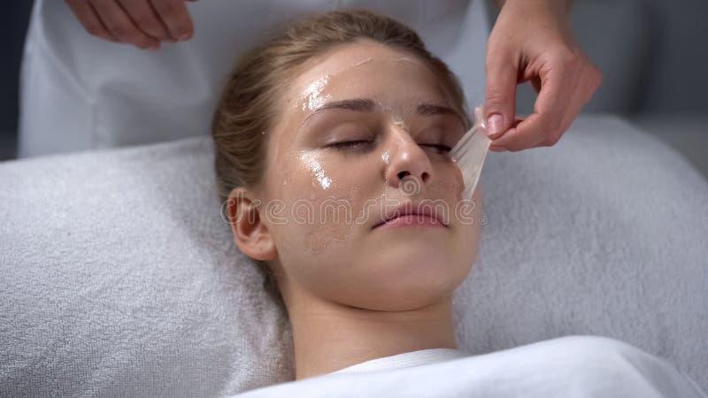 Kosmetologen som tar bort rest av maskeringen från flickor, vänder mot, djup lokalvård av por arkivfoton