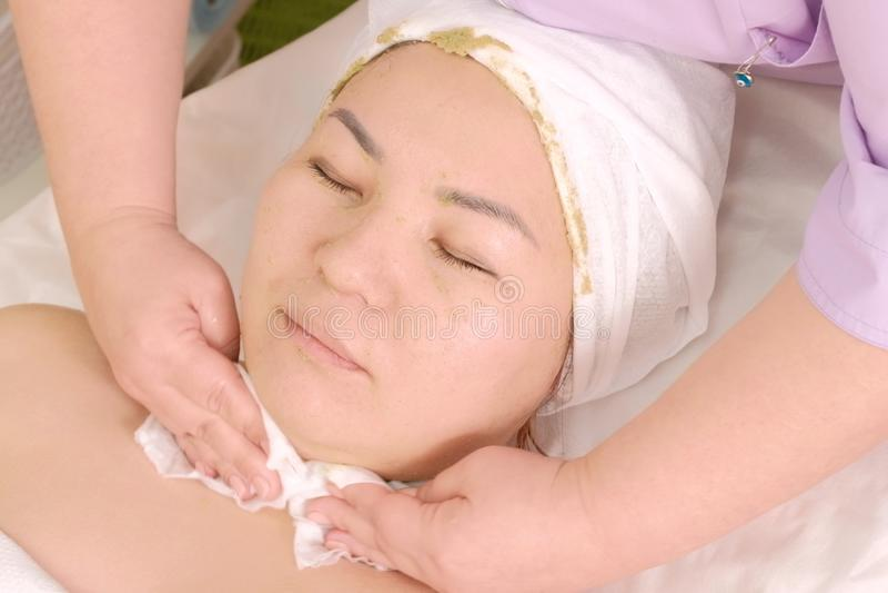 Kosmetologen torkar flickans framsida Ung asiatisk kvinna i en skönhetsalong Ansikts- maskering för gröna alger royaltyfri bild