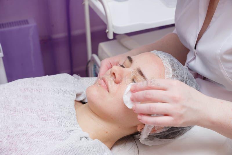 Kosmetologen tv?ttar kvinnans framsida genom att anv?nda bomullsblock royaltyfria bilder