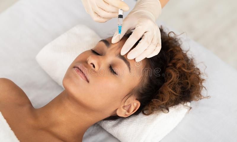 KosmetologExpert Injecting In kvinnlig panna royaltyfri fotografi