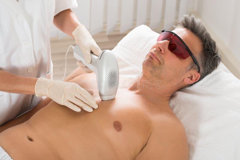 KosmetologGiving Laser Epilation behandling till mannen arkivbild