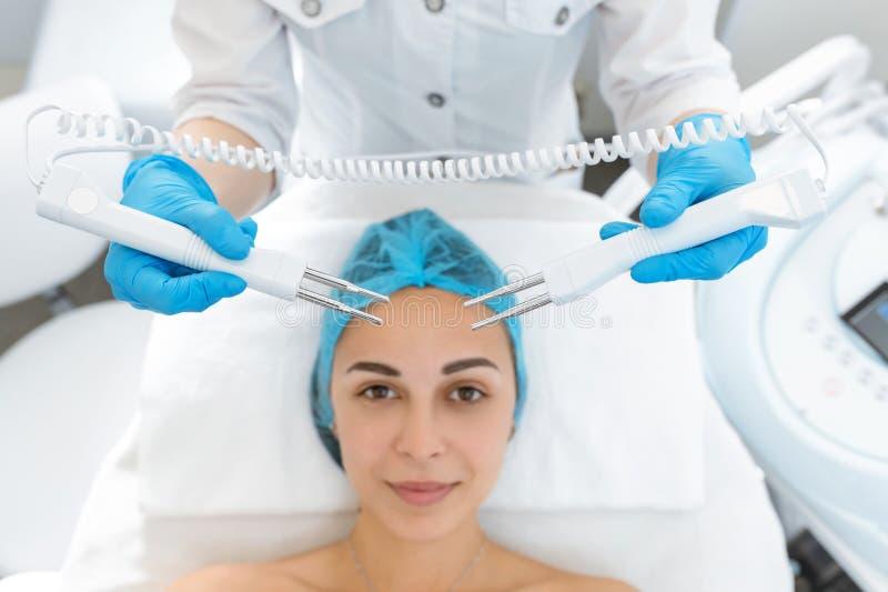 Kosmetologtillvägagångssätt av microcurrent terapi av patientens framsida En ung flicka genomgår en kurs av brunnsortbehandlingar royaltyfria foton
