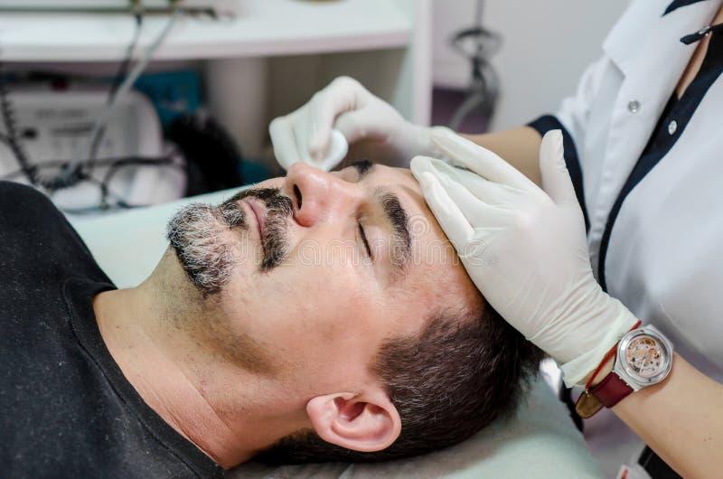 Kosmetologtillvägagångssätt som rentvår framsidamän royaltyfria foton