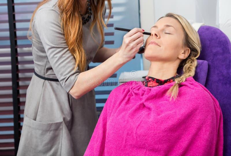 KosmetologUsing Applicator On kunds framsida i mottagningsrum royaltyfri bild