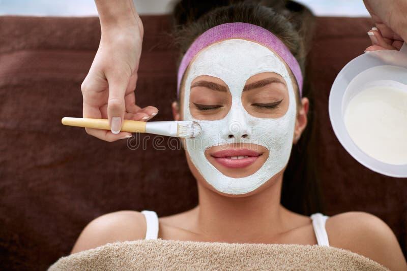Kosmetyczka stosuje twarzową maskę twarz kobieta zdjęcie royalty free