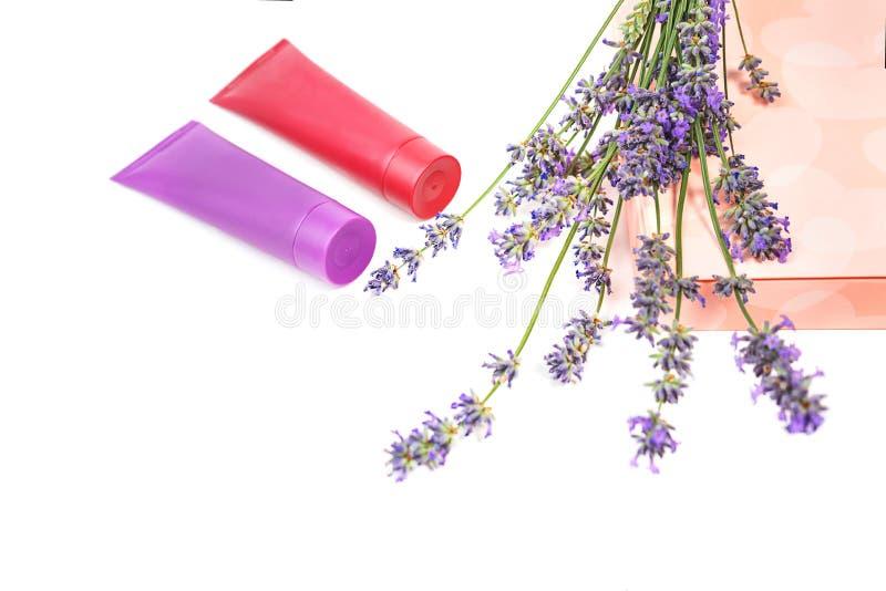 Kosmetyczna śmietanka i lawendowi kwiaty, prezenta pudełko z cukierkami na białym tle, odizolowywającym obrazy stock