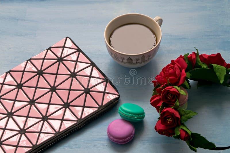 Kosmetyczna torba, filiżanka kawy, róże i macaroons na błękitnym tle, zdjęcia stock