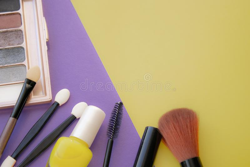 kosmetyczne akcesoria Szczotkuje dla rumiena, szczotkuje, lakier na kolorze żółtym, purpurowy tło zdjęcia stock