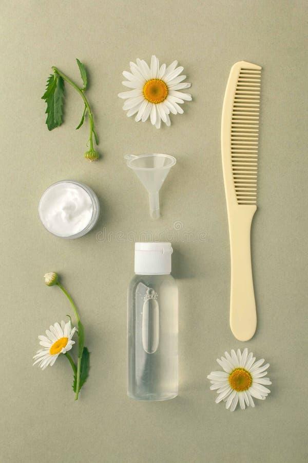 Kosmetyczni butelka zbiorniki z hermal rumiankiem kwitną Pustą etykietkę dla oznakować egzamin próbnego, Naturalny organicznie pi zdjęcie royalty free