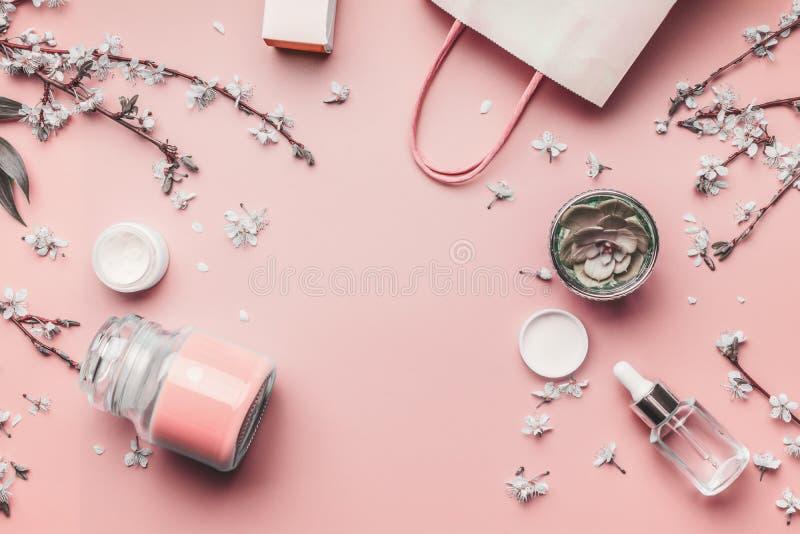 Kosmetyka i skóry opieki pojęcie Różnorodni twarzowi produkty na pastelowych menchii tle z czereśniowym okwitnięciem i liśćmi, od obrazy stock