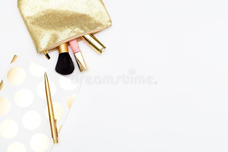 Kosmetyki dla makijażu i notatnik z piórem w złocistym kolorze na w obrazy royalty free