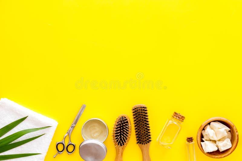 Kosmetyki dla włosianej opieki z jojoba, argan lub kokosowym olejem w butelce na żółtym tło odgórnego widoku mockup, fotografia stock