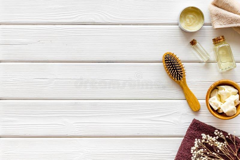 Kosmetyki dla włosianej opieki z jojoba, argan lub kokosowym olejem w butelce na białego drewnianego tła odgórnym widoku w górę, zdjęcia royalty free