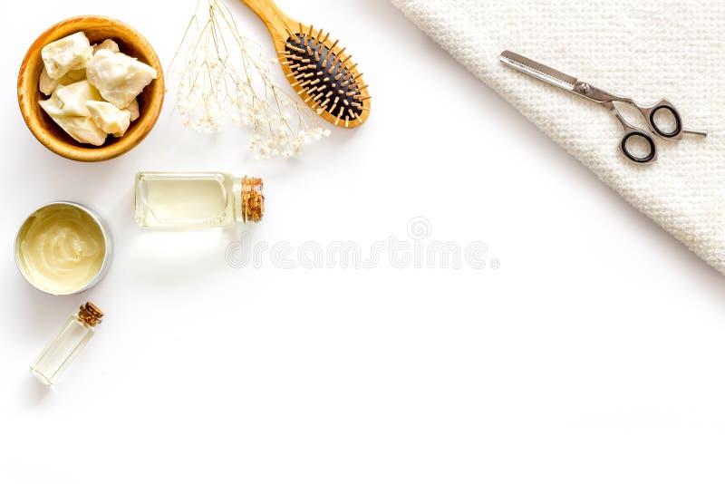 Kosmetyki dla włosianej opieki z jojoba, argan lub kokosowym olejem w butelce na białym tło odgórnego widoku egzaminie próbnym w  fotografia stock