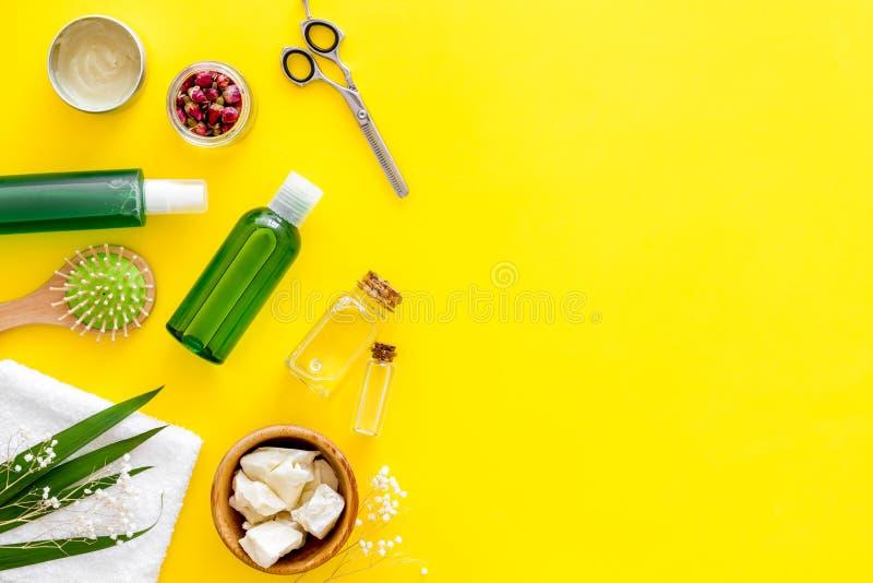 Kosmetyki dla włosy z jojoba, argan lub kokosowym olejem w butelce, nożyce, muśnięcie na żółtym tło odgórnego widoku mockup zdjęcia stock