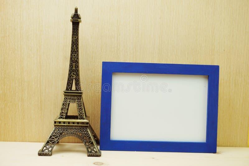 Kosmiczna ramka fotograficzna drży z pamiątką wieży Eiffela na drewnianym tle fotografia royalty free