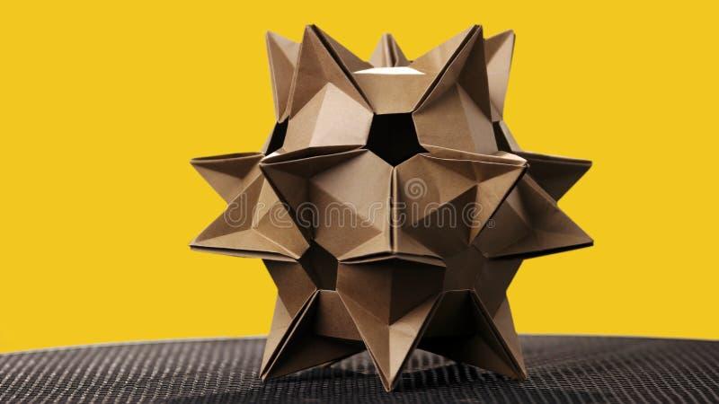 Kosmiskt diagram f?r origami p? gul bakgrund royaltyfria foton
