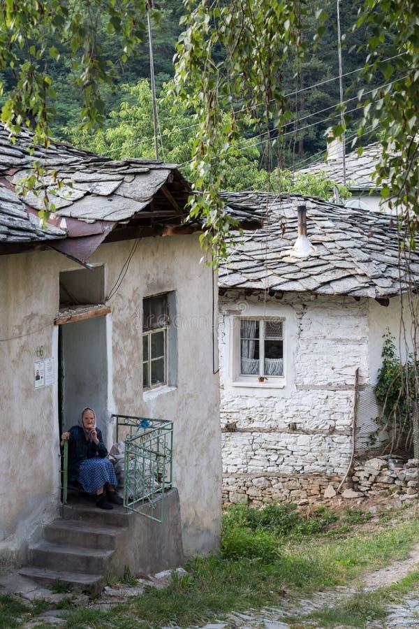 Kosovo Bulgarien - Juli 21, 2017: den oidentifierade gamla bulgariska kvinnan sitter framme av hennes genomsnittliga hus arkivbilder