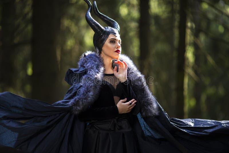 Kost?m-Drama-Spiel K?nstlerische Maleficent Frau in der schwarzen Kleidung und in den H?rnern im Fr?hjahr Forest Posing mit welle stockfotografie