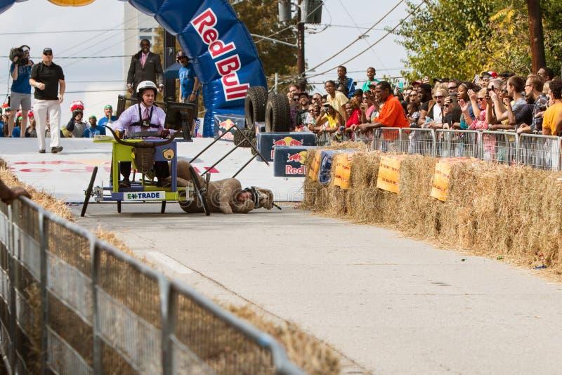 Kostümierter Konkurrent fällt stark vom Fahrzeug im Seifenkistenrennen stockbild