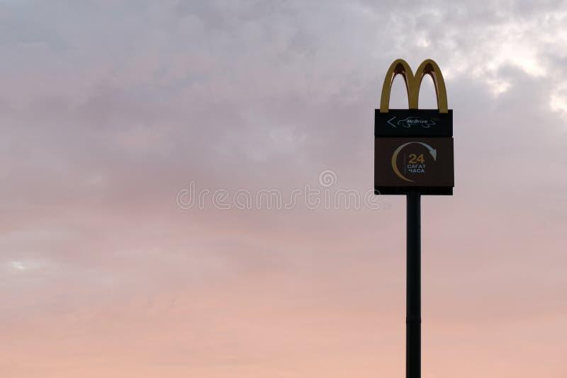 Kostanay, Kazachstan, Vrijdag Juli 13, 2018, het embleem van McDonald ` s hoog in de hemel bij dageraad of schemer Silhouet De ru royalty-vrije stock afbeelding