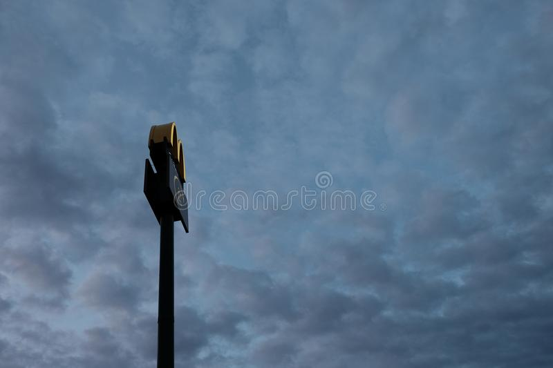 Kostanay, Kazakhstan, Friday July 13, 2018, McDonald`s logo on a pillar high in the sky at dawn or dusk. Copy space. Silhouette. Kostanay, Kazakhstan, Friday stock images