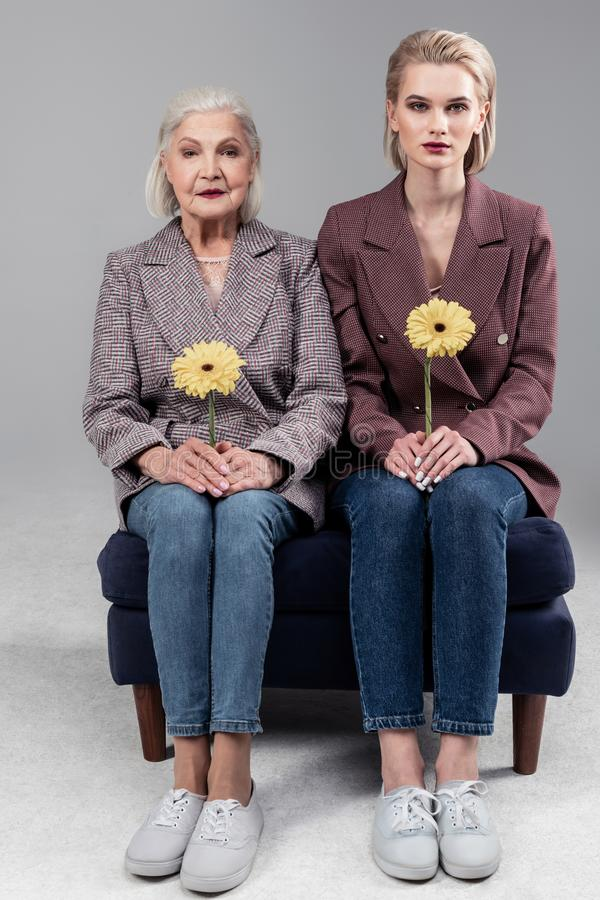 Kostbare schöne saubere Frauen, die auf wenigem Sofa nah an einander sitzen stockbilder