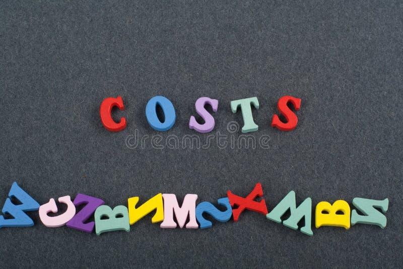 Kosten fassen auf dem schwarzen Bretthintergrund ab, der von den hölzernen Buchstaben des bunten ABC-Alphabetblockes verfasst wir stockbild