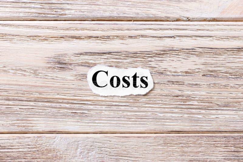 Kosten van het woord op papier Concept Woorden van kosten op een houten achtergrond royalty-vrije stock foto