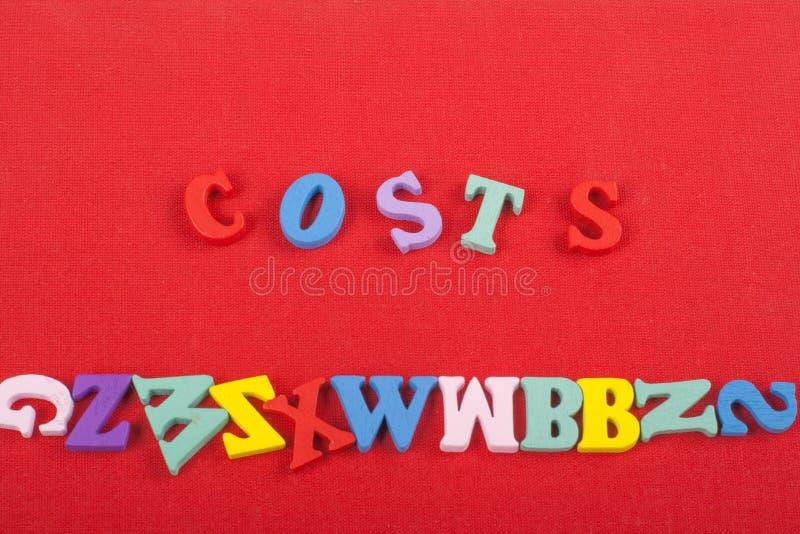 Kostenwort auf dem roten Hintergrund verfasst von den hölzernen Buchstaben des bunten ABC-Alphabetblockes, Kopienraum für Anzeige stockfotografie