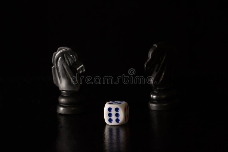 Kostka do gry i czarni szachowi konie na ciemnym tle fotografia stock