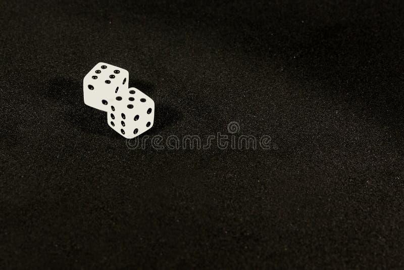 Kostka do gry na stole na czarnym tle zdjęcia stock