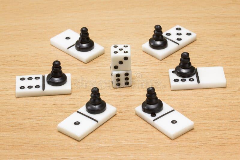 Kostka do gry wokoło których domina i czarni szachowi pionkowie zdjęcia royalty free