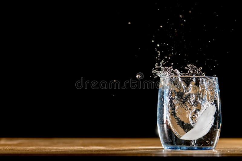 Kostka lodu spada w wodę i bryzgać obrazy royalty free