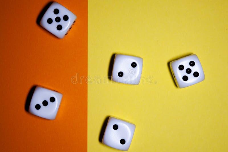 Kostki do gry mieszkanie kłaść na Żółtym i pomarańczowym tle zdjęcia stock