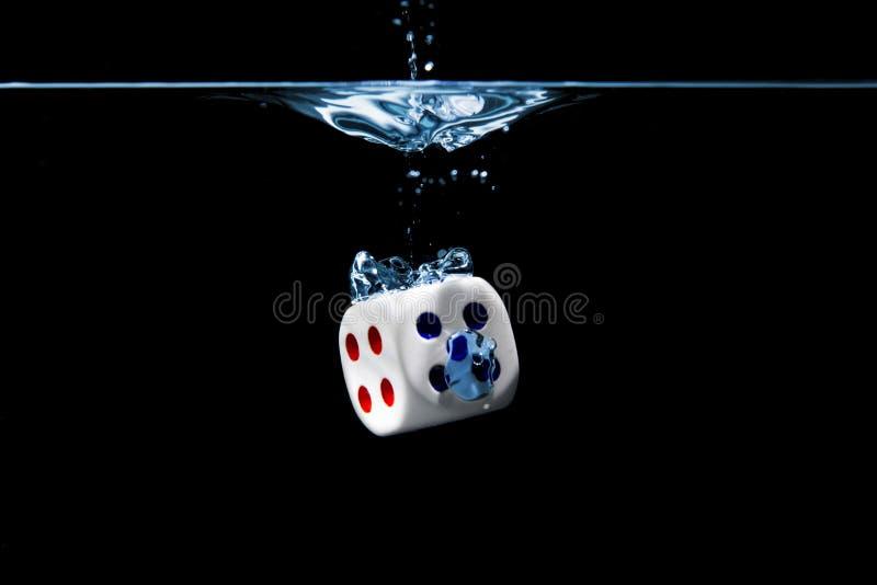 Kostki do gry z liczbami cztery i pięć twarzy w wodzie z czarnym tłem obrazy royalty free