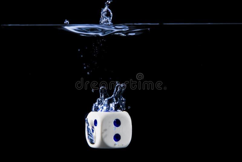 Kostki do gry z numer dwa stawiają czoło w wodzie z czarnym tłem obrazy stock