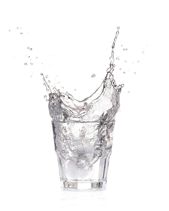 Kostki lodu bryzga w szkło woda, odosobnionego zdjęcia stock
